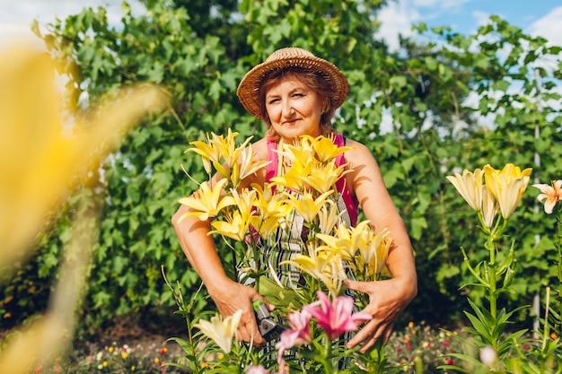 年配の女性が庭で花を抱き締めます。中年の庭師は剪定でユリを切り取ります。ガーデニングのコンセプト