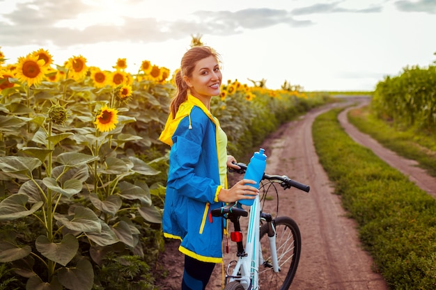 Молодой счастливый велосипед катания велосипедиста женщины в поле солнцецвета. летняя спортивная деятельность. здоровый образ жизни