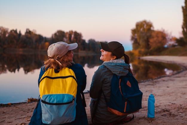 秋の川の土手でリラックスしたバックパックと観光客のカップル