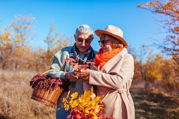 秋の森を歩く年配のカップル。