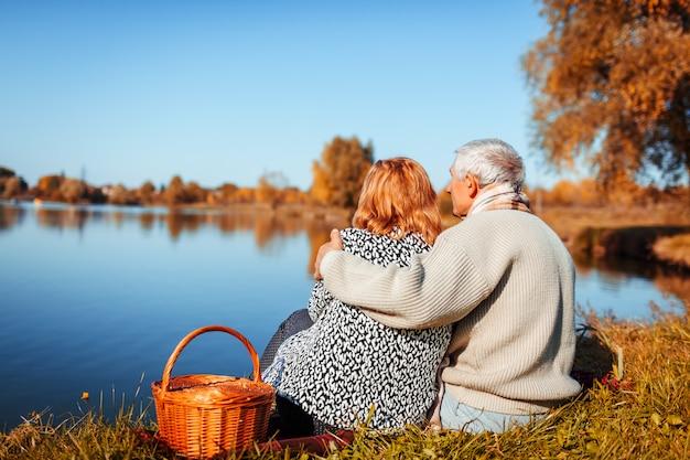 秋の湖でピクニックを持っている年配のカップル。