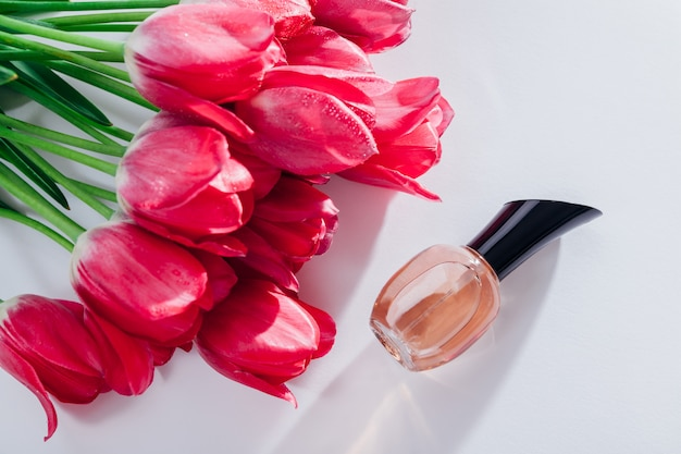 ピンクのチューリップと香水の瓶。花の香り。天然化粧品のコンセプトです。女性への贈り物