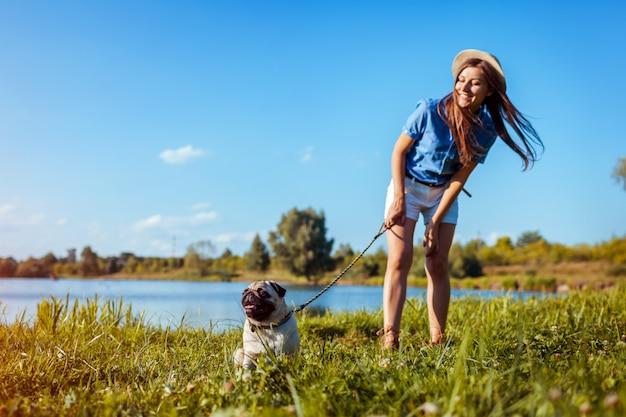 川のそばに座ってパグ犬。マスターの命令を待っている幸せな子犬。犬と女が屋外で低温