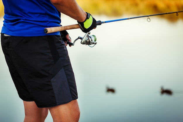 若い男が日没で川で釣り。ロッドを保持している漁師のクローズアップ。釣り道具。紡糸