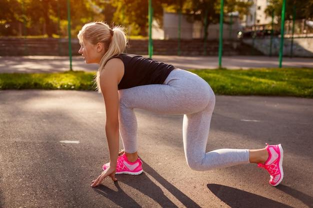 スポーツグラウンドで早いスタートに降りる若い女性ランナー