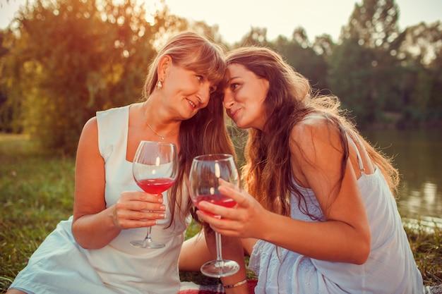 夕暮れ時の夏の川で大人の娘とワインを飲む母。