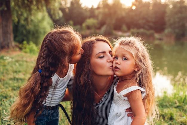 母と娘が屋外で抱き合ったりキスしたりします。夕暮れ時の夏の川で歩く家族。