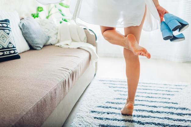 シルクのガウンを着て、結婚式の日に花嫁、自宅で青い靴を保持している若い女性