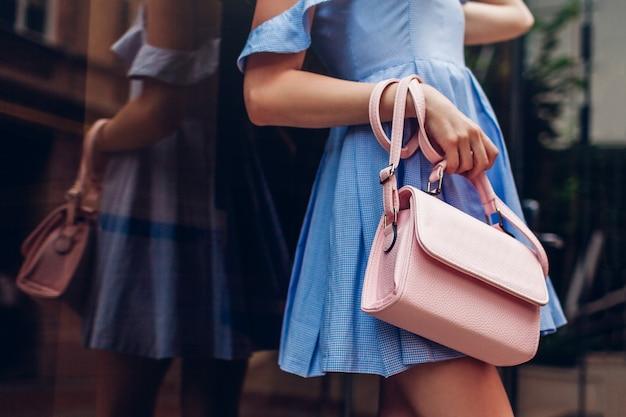スタイリッシュな女性のハンドバッグのクローズアップ。屋外の美しいアクセサリーを保持しているファッショナブルな女性。