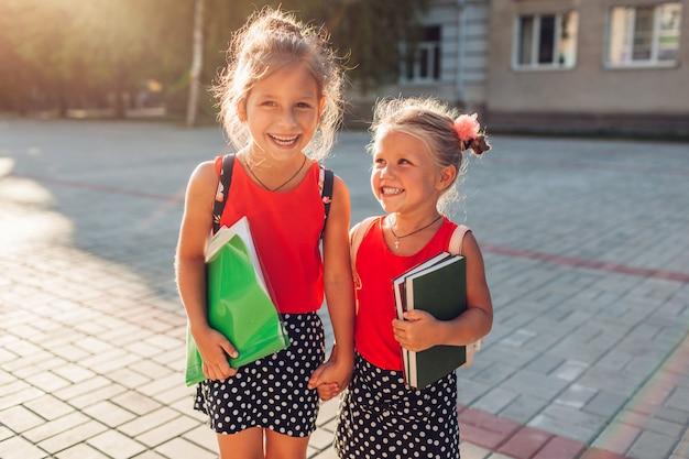 バックパックを着て本を持って幸せな姉妹