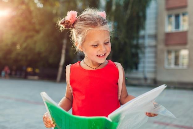 バックパックを着てファイルを保持している幸せな女の子