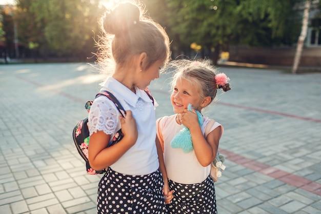 バックパックを着て手を繋いでいる幸せな姉妹