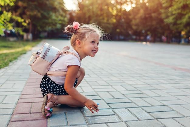 バックパックを着て、チョークで描くの幸せな女の子