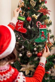 サンタ帽子をかぶって、自宅のキャンディー杖でクリスマスツリーを飾る若い女性。