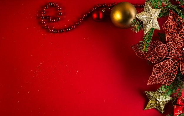 モミの木とおもちゃで飾られたクリスマスと新年の赤い背景