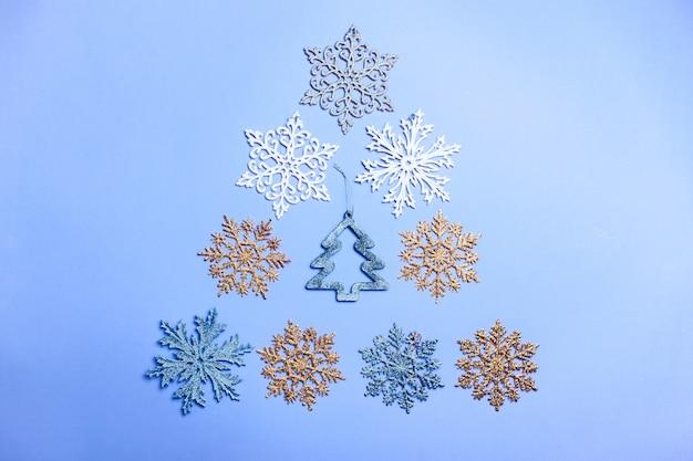 Синий фон рождество и новый год с елкой из игрушек. космос