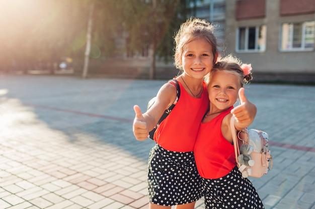 バックパックを着て、親指を現して幸せな姉妹の女の子。屋外の校舎を笑顔の子供たち。教育