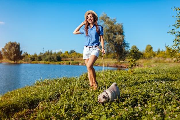 川でパグ犬と一緒に歩いている幸せな女。犬と屋外で身も凍る女性