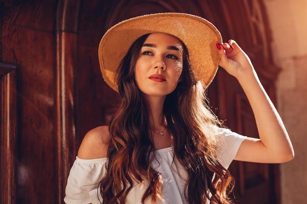 麦わら帽子をかぶっている長い髪の若い美しい女性の屋外のポートレート。ファッションモデル。閉じる