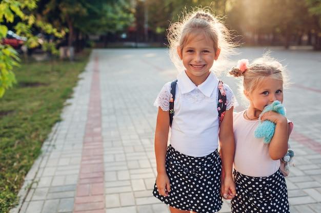 バックパックを着て手を繋いでいる幸せな姉妹の女の子