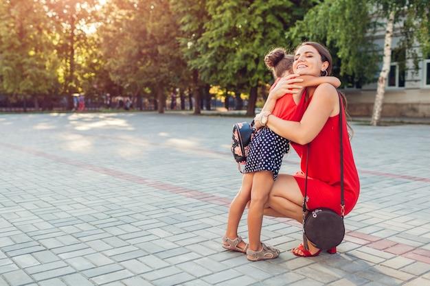 Счастливая мать, встреча ее дочь после занятий на открытом воздухе в начальной школе.