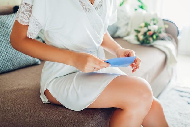 シルクのドレッシングガウンと誓いの封筒を開く若い女性