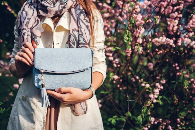 スタイリッシュなバッグを押しながらトレンディな服を着ている女性。