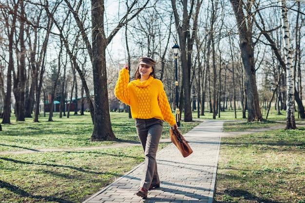 スタイリッシュなハンドバッグを押しながら秋の服を着た若い女性