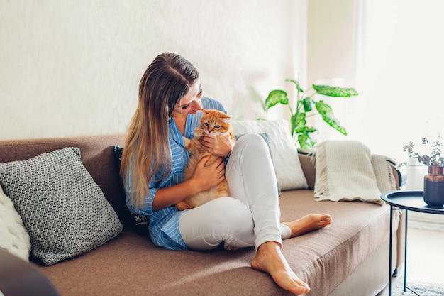 Играя с кошкой дома. молодая женщина, сидя на диване с домашним животным.
