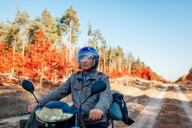 Самокат катания старшего человека на дороге леса осени. водитель в шлеме катается на мопеде