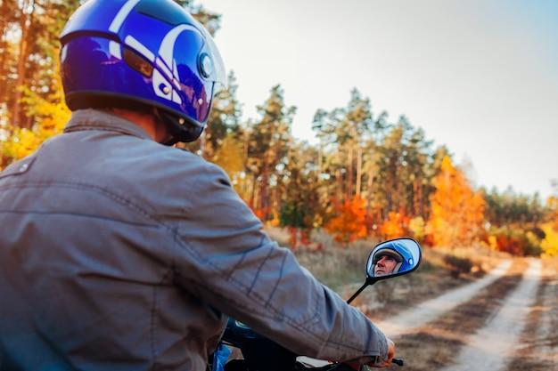 秋の林道で年配の男性人乗るスクーター。ヘルメットに乗ったドライバーの原付け