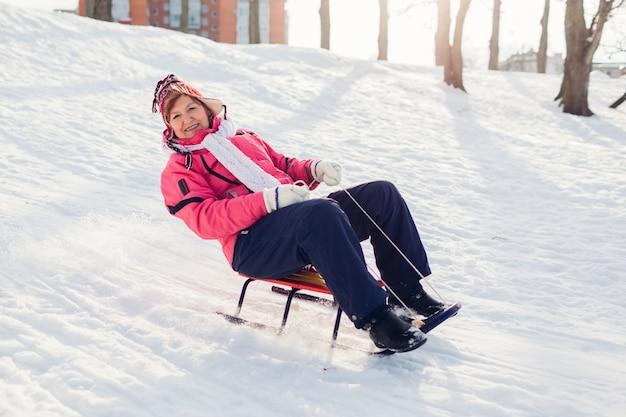 そり。冬の公園でそりで楽しんでいる年配の女性。冬のアクティビティ