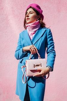 美容ファッションモデル。スタイリッシュなハンドバッグを押しながら青いコートを着ている女性。秋の女性服とアクセサリー。