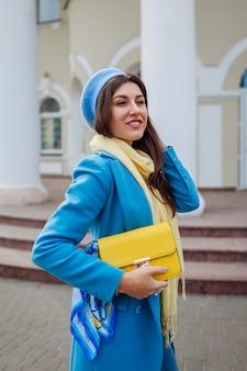 美容ファッションモデル。スタイリッシュなハンドバッグを保持しているトレンディな青いコートの若い女性。秋の女性服とアクセサリー。