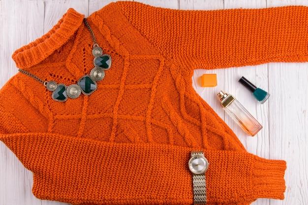 アクセサリーと化粧品のオレンジ色のセーター。木製の背景に女性の服