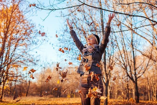 秋。秋の森の葉を投げる中年の女性。屋外楽しんで年配の女性