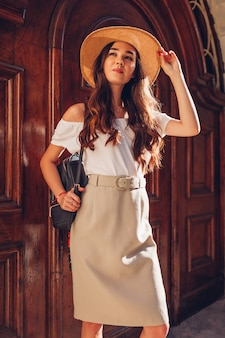 ファッションモデル。麦わら帽子をかぶっているとバックパックを保持している若い美しい女性の屋外のポートレート。