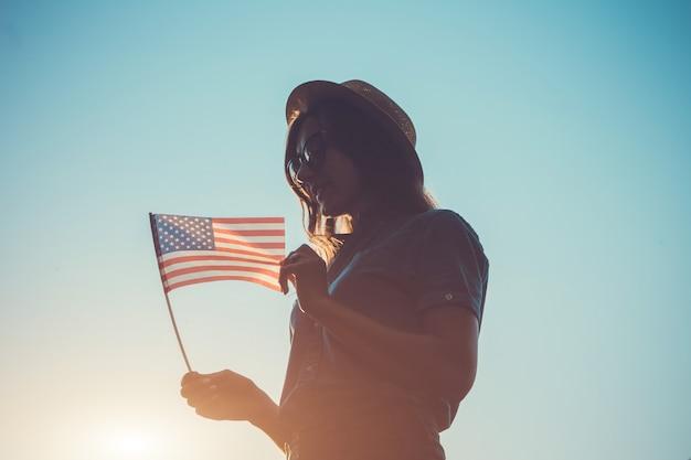 アメリカの国旗を保持している女性。アメリカ独立記念日を祝う