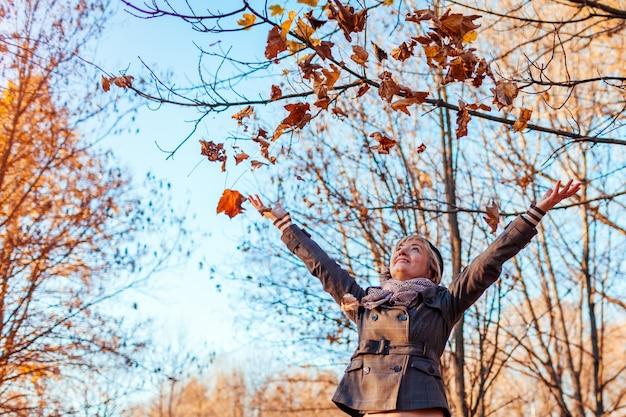 秋のアクティビティ。秋の森で葉を投げる中年の女性。屋外楽しんで年配の女性