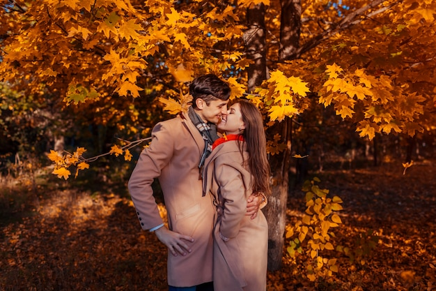 愛の若いカップルは、落ち葉の中で秋の森を歩きます。ハグするスタイリッシュな人々