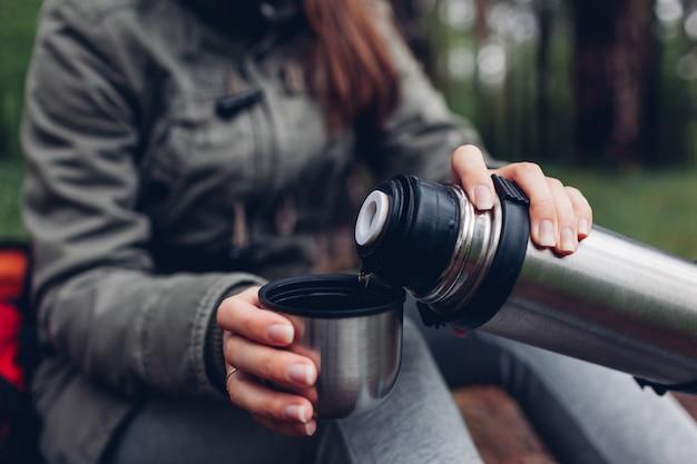女性観光客は、春の森の魔法瓶から熱いお茶を注ぐ。キャンプ、旅行、スポーツコンセプト