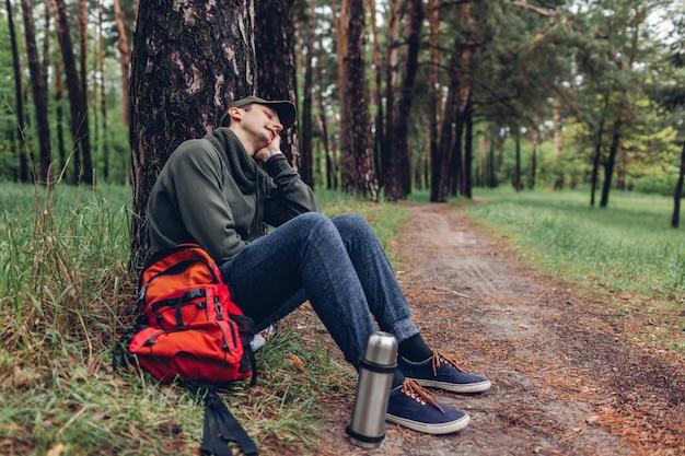 春の森で寝ている疲れた男の観光客。旅行者は休憩のために立ち止まった。キャンプ、旅行、スポーツコンセプト