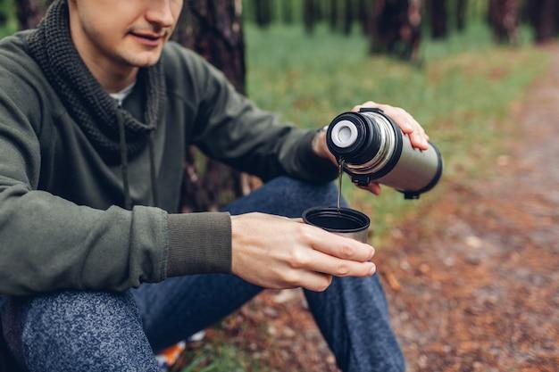男の観光客は、春の森の魔法瓶から熱いお茶を注ぐ。キャンプ、旅行、スポーツコンセプト