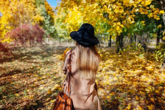 秋のバイブ。落ち葉の中で秋の森を歩く若い女性。帽子をかぶっているスタイリッシュな女の子