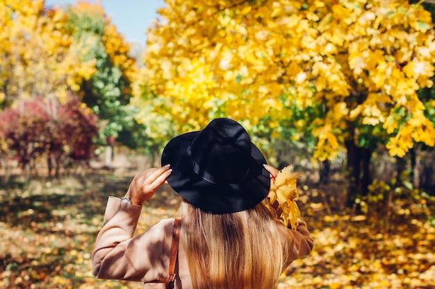 秋のバイブ。落ち葉の中で秋の森を歩く若い女性。旅行者は自然を賞賛します