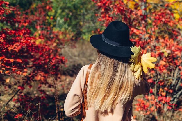 Осенние флюиды. молодая женщина гуляя в пущу осени среди красных листьев. путешественник восхищается природой
