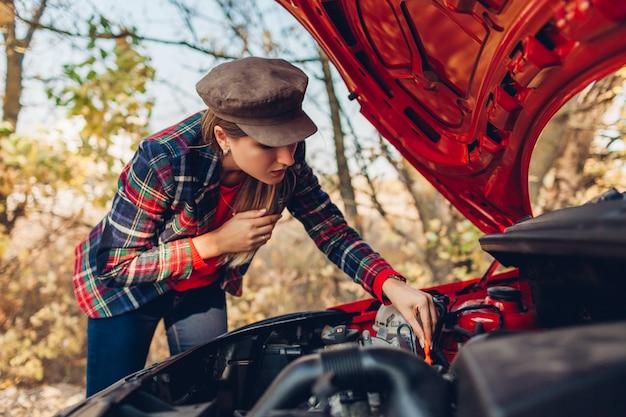 車の破損。女性は道路で停止し、マシンオイルのレベルをチェックする彼女の自動車のボンネットを開けた