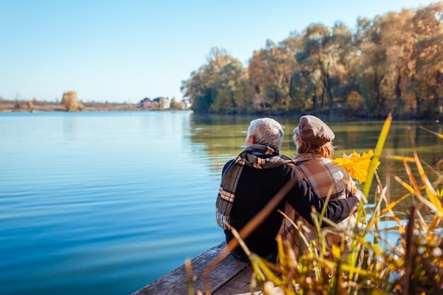 秋の湖でリラックスした年配のカップル。幸せな男と女の自然を楽しんで、桟橋に座ってハグ