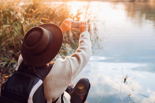 Турист с рюкзаком фотографировать, используя смартфон реки на закате. женщина путешествует, любуясь осенней природой