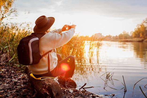 夕暮れ時の川のスマートフォンを使用して写真を撮るバックパックの観光客。秋の自然を眺めながら旅行する女性